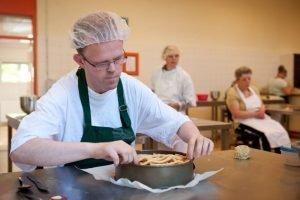 Medewerker van Bakkerij de Rode Luifel maakt een appeltaart