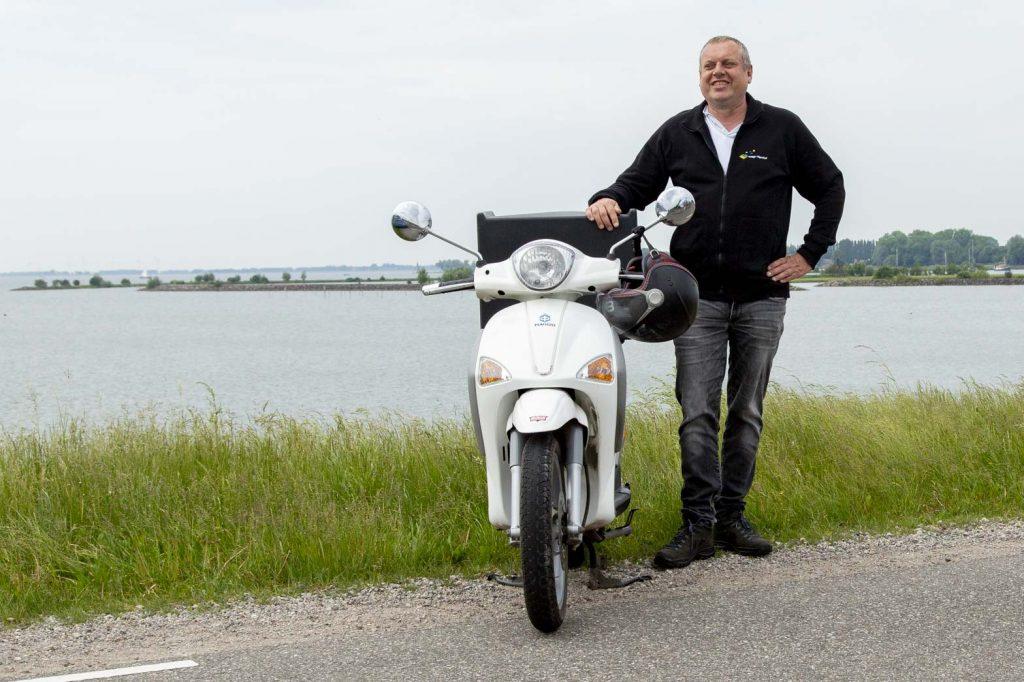 Marcel staand naast zijn brommer op de dijk langs het IJsselmeer bij Hoorn