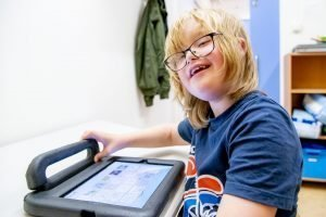 Kind werkt met iPad en kijkt lachend in de camera