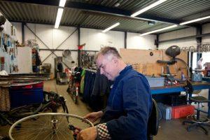Man repareert spaken van een fietswiel bij 't Freem in Zwaag