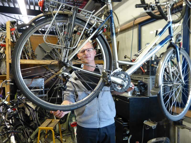 Man werkt aan een fiets bij 't Freem in Zwaag