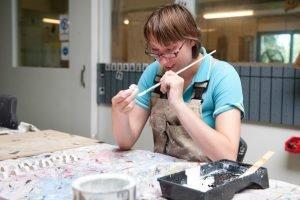 Vrouw schildert hout bij Houdt van Hout in Zwaag