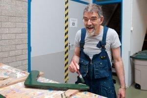 Man schildert hout bij Houdt van Hout in Zwaag
