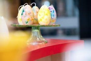 Kaarsen in de vorm van een ei op een glazen schaal
