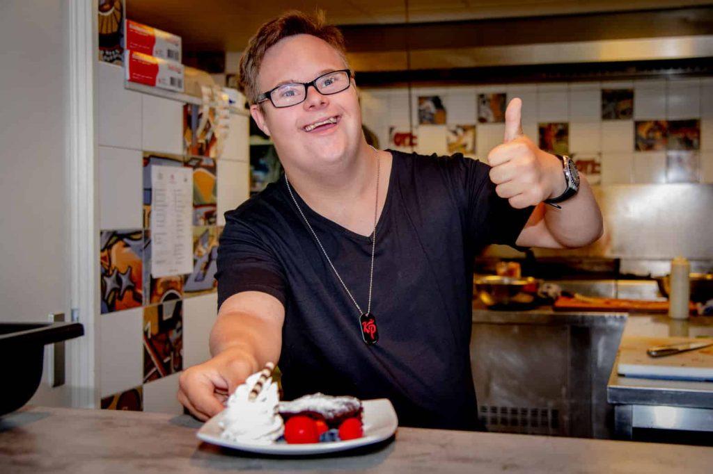 Client serveert gerecht uit keuken en steekt zijn duim omhoog