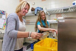 Kirsten en shirley doen de afwas in een afwasmachine