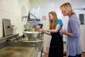 Shirley frituurt kroepoek terwijl Kirsten meekijkt
