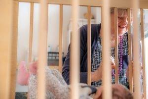 Jolanda kijkt vertederd naar een van de kinderen in de box van het kinderdagverblijf