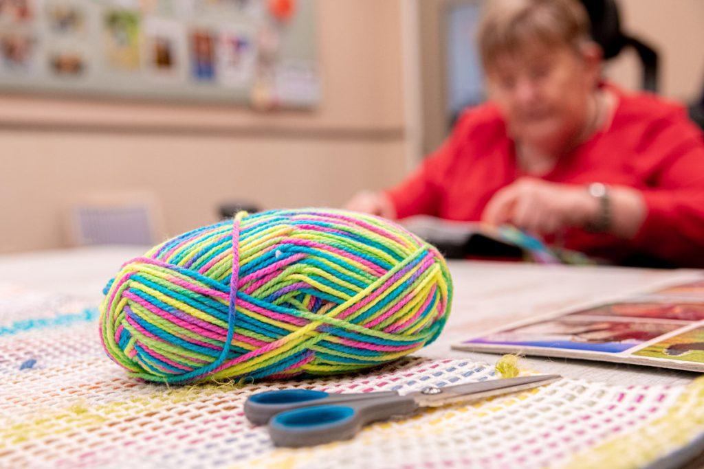 Bol gekleurde wol en een schaar. Annegien borduurt in de achtergrond
