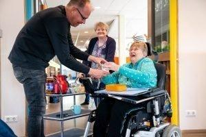 Meester Niels pakt zijn koffie aan van Annegien terwijl Jolanda lachend toekijkt