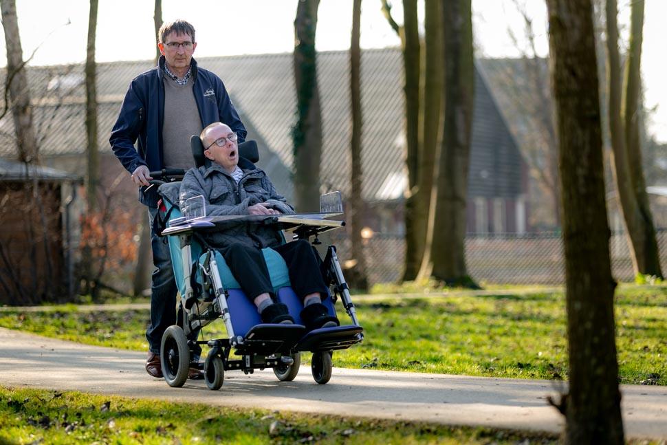 Dik duwt de rolstoel van John tijdens het wandelen