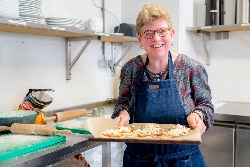 Marijke draagt een ovenschaal met minipizza's