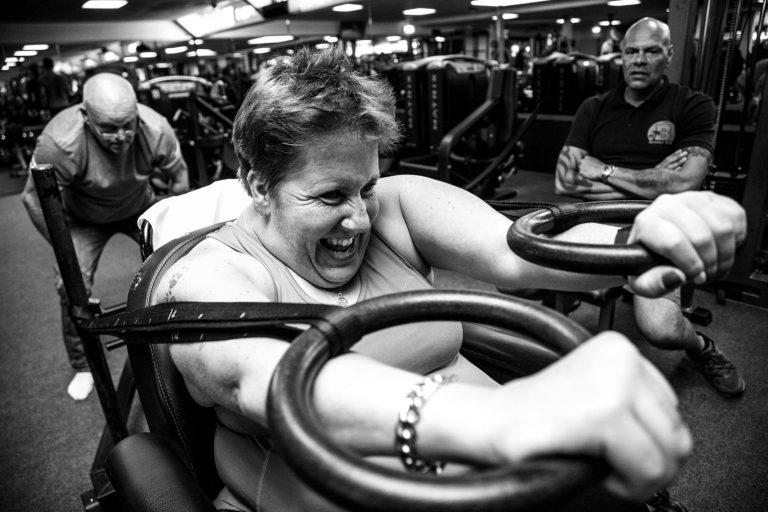 Muriel traint haar armspieren terwijl trainers toekijken
