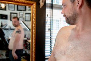 Tomas bekijkt zijn tattoo in de spiegel bij tattooshop Nothing to prove