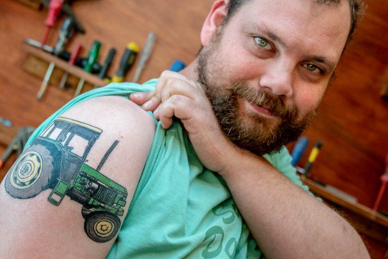 Tomas toont trots zijn tattoo terwijl hij in zijn schuurtje staat