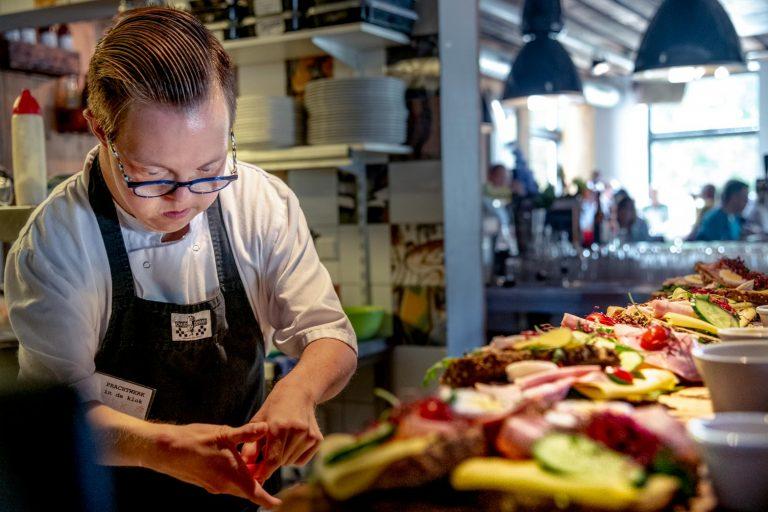 Nicj maakt lunchgerechten klaar voor gasten in het restaurant