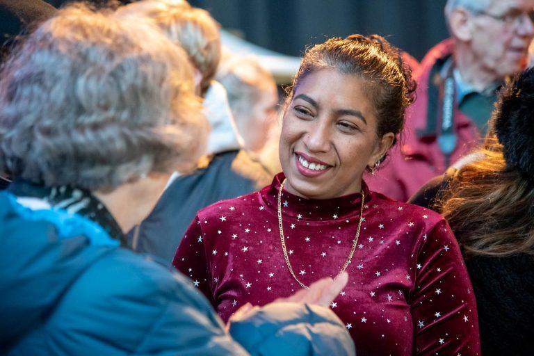 Soenita helpt een mevrouw op de Kerstmarkt