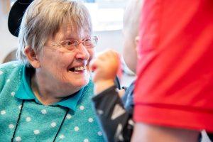 Annegien lacht naar een van de kinderen van het kinderdagverblijf