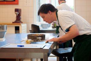 Medewerker van Bakkerij de Rode Luifel rolt deeg voor een appeltaart