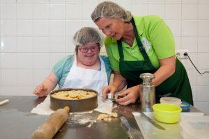 Medewerkers van Bakkerij de Rode Luifel Bakken een appeltaart