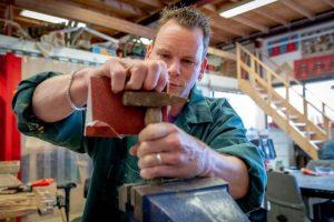 Man schuurt een roestige hamer met schuurpapier