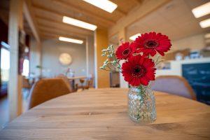 Vaasje met rode bloemen op een tafeltje in het theehuis