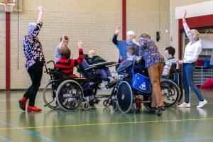 Vrijwilligers en cliënten in rolstoelen in een gymzaal