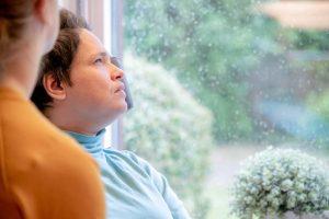 Inge kijkt naar buiten door een beregend raam van de Steg