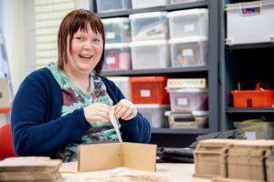 Vrouw vouwt lachend papieren hoesjes